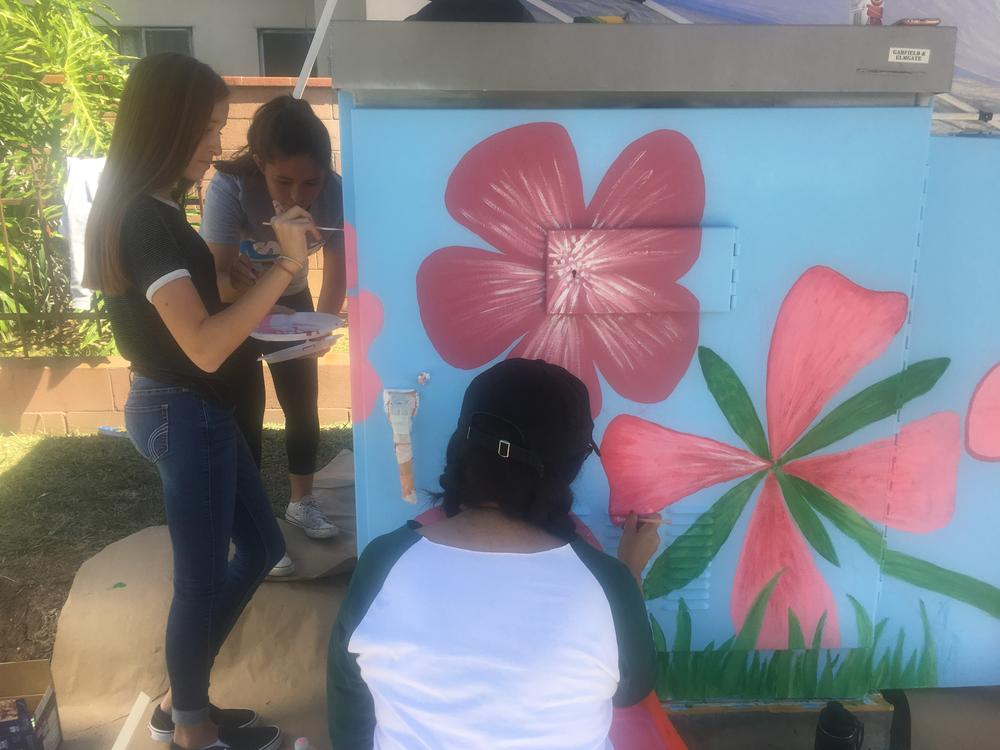 Art students painting an electrical box.